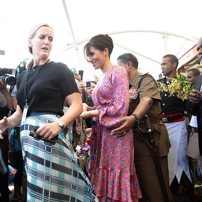 Duchess Meghan had her visit to Suva Market in Tonga cut short when her security team became worried about crowds. She was still smiling, though, as her female guard rushed her to the car.