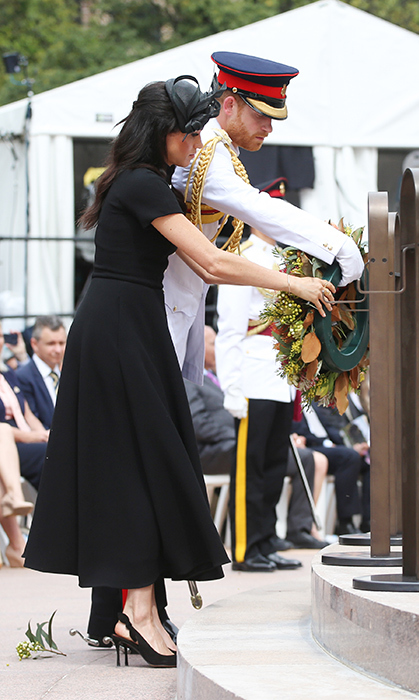 The royal couple paid their respects at the ANZAC Memorial in Hyde Park, laying a wreath out of respect for the fallen soldiers. Prince Harry wore his tropical uniform of the Blues and Royals, while Meghan kept her outfit all black in a midi Emilia Wickstead dress.