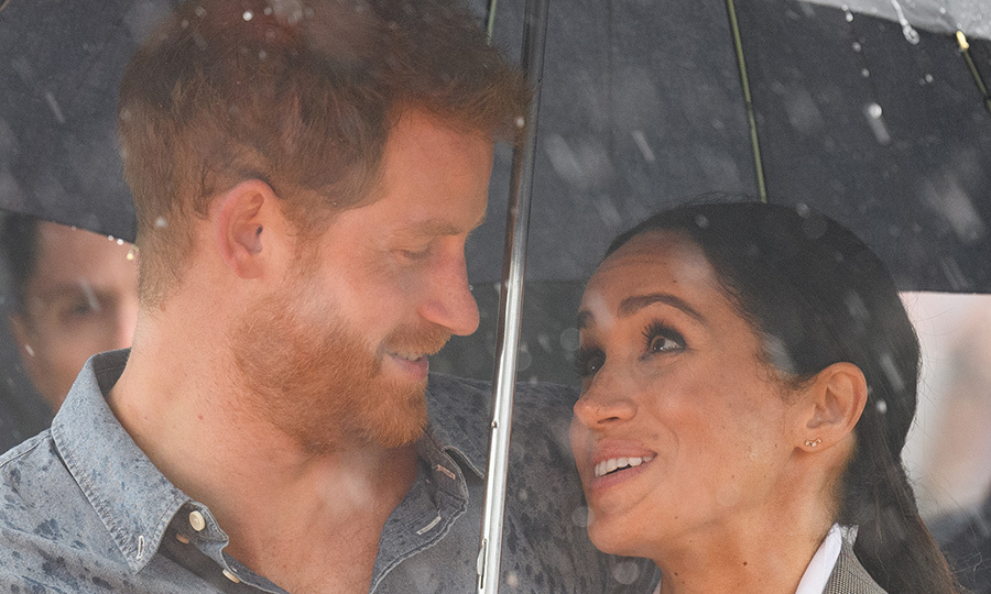 On a visit to Victoria Park in Dubbo, the rain really came down as the Duke and Duchess of Sussex stole a sweet moment under their umbrella. Meghan later held the umbrella over Prince Harry's head while he made a speech.