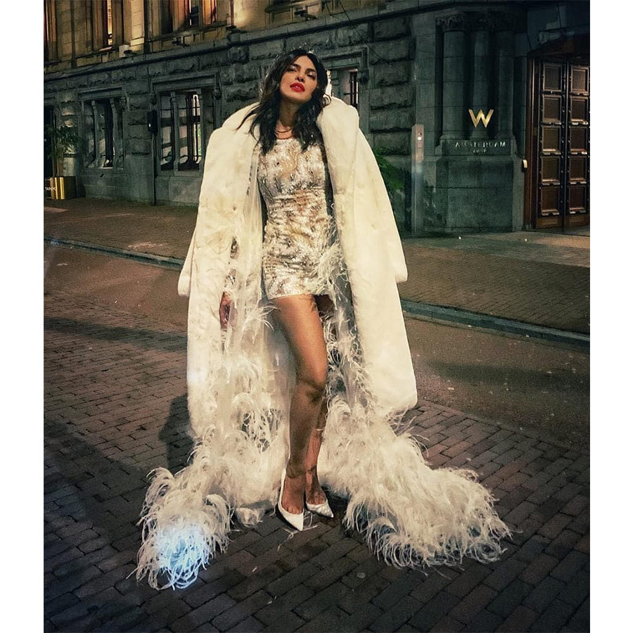 Priyanka Chopra was pure glam outside the W in Amsterdam during her bachelorette party wearing a white ensemble by Georges Chakra with a faux fur topper!