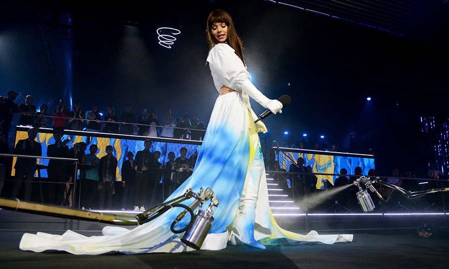 Hailee Steinfeld wore eight stunning looks as host of the MTV EMAs on Nov. 4, but perhaps the most eye-catching was the white ensemble that was spray painted live with blue and yellow paint during the show in Bilbao, Spain.