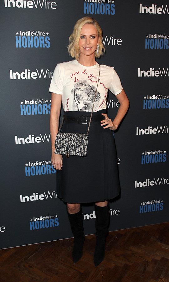 Oscar winner Charlize Theron paired a casual t-shirt with a knee-length skirt and high boots at the IndieWire Honors on Nov. 1 in LA, where she received the Maverick Award. 
