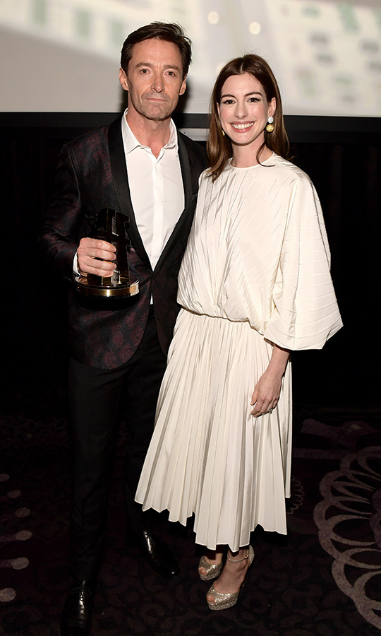 "Clad in voluminous Valentino, Anne Hathaway posed with Hugh Jackman after introducing his Hollywood Actor Award at the HFAs, telling a funny story about the industry's nicest actor ""losing it"" on the set of their 2012 film <em>Les Miserables</em>.
