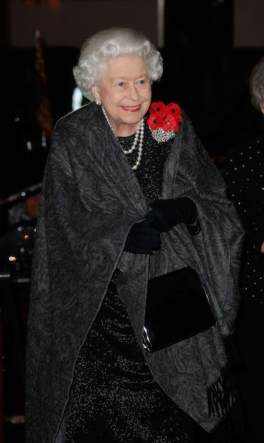 The Queen was all smiles as she arrived at the Royal Albert Hall. Her Majesty wore black and grey, two strands of pearls, four poppies and black gloves, carrying her signature patent black bag.