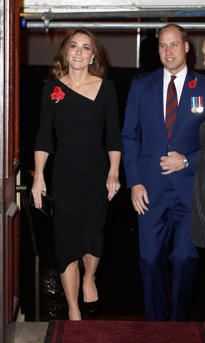 Duchess Kate and Prince William arrived together, showing off their megawatt smiles. Ever the fashion maven, Kate dazzled in a simple black dress by Meghan's friend Roland Mouret with a stunning asymmetrical neckline.