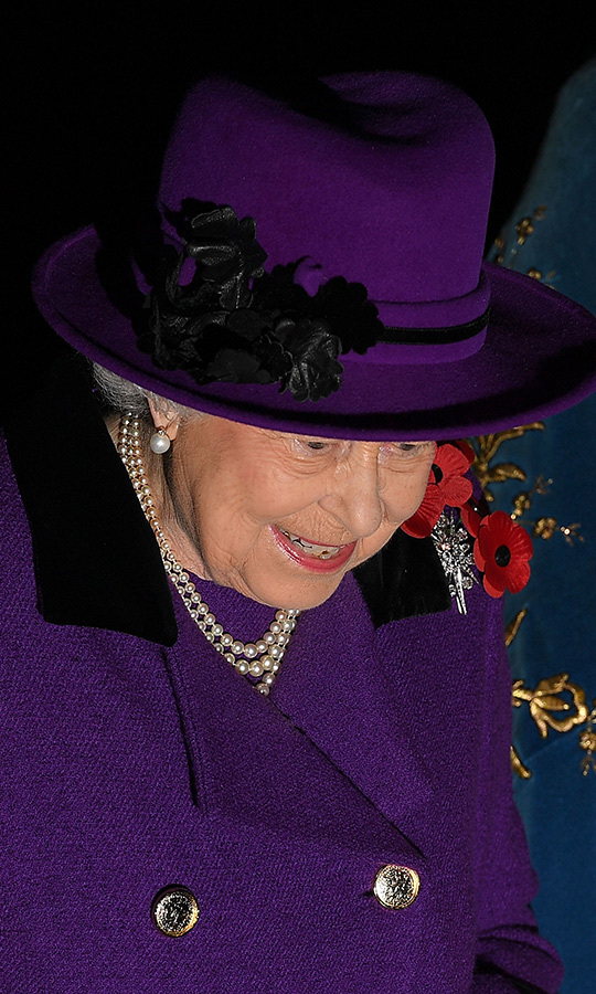 The Queen accessorized her regal look with a tri-strand pearl necklace and matching earrings as well as a pin featuring four poppies.