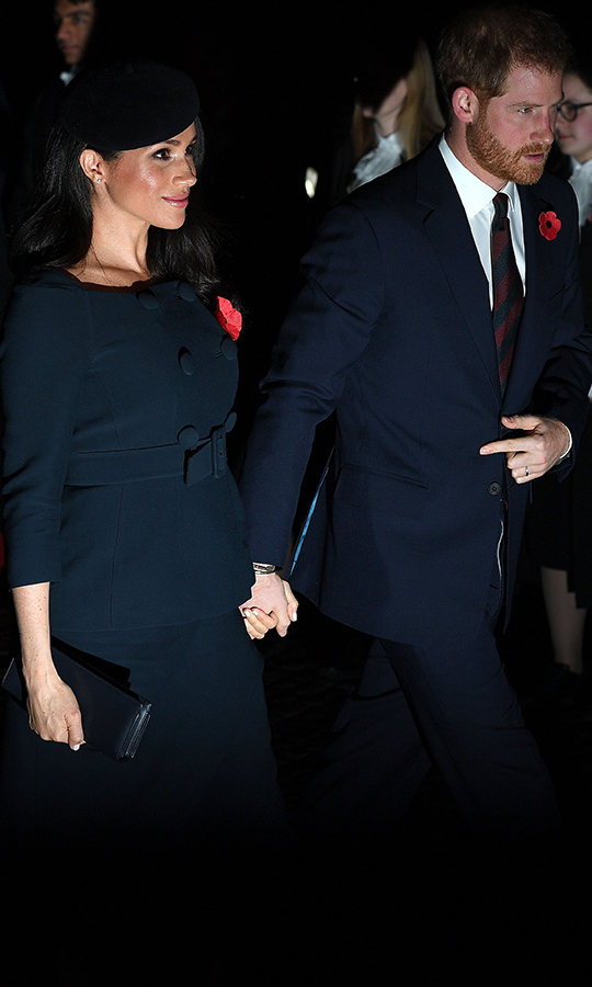 The duchess previously wore a similar double-breasted ensemble to an awards event with her husband and the Queen, a pink Prada design that featured a flared skirt instead of tonight's slim silhouette. Prince Harry was perfectly coordinated in a dapper navy suit with a striped burgundy and blue tie.