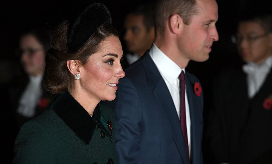 Kate wore her go-to accessory, an oversized headband, this time in black velvet to match the velvet cuffs and collar on her coat. She accessorized with floral pearl earrings and wore a rosy glow on her cheeks and a smokey eye. 