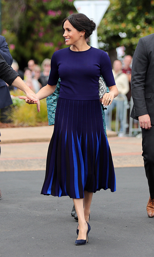 The duchess dazzled in a Givenchy ensemble as she changed into her second look on the final day of the couple's royal tour, heading to a walkabout in Rotura wearing a blue short-sleeved sweater with a two-tone pleated midi skirt. She kept her Manolo Blahnik BB pumps on as well as the Boh Runga earrings that were a gift from New Zealand Prime Minister Jacinda Arden. 