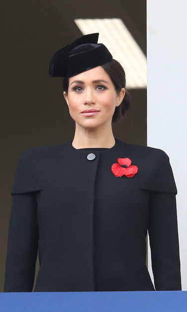 "As Meghan watched her veteran husband Prince Harry lay a wreath at the Cenotaph on Remembrance Sunday, she wore a black coat featuring a short-sleeved overlay with a velvet hat tilted atop her head. The mom-to-be wore her hair in a side chignon to show off her Vanesssa Tugenthaft ""Precious"" earrings. 