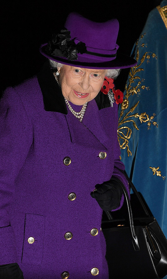 The Queen looked beautiful in a double-breasted purple coat with a black collar and a purple hat embellished with black blooms. She toted her ever-present black handbag and wore black gloves to keep the chill at bay. 