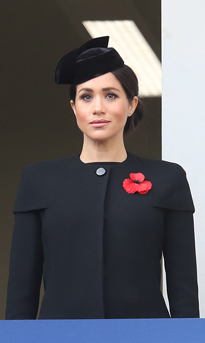 "Earlier that day, Duchess Meghan looked chic in an elegant Givenchy black coat and black velvet hat. She accessorized the look with the ""Precious"" earrings by Vanessa Tugenthaft and an oversized poppy.