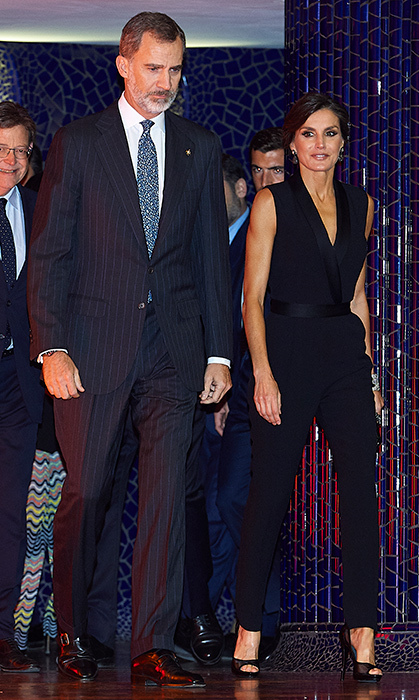 "On Nov. 7, Queen Letizia stepped out with King Felipe VI to attend ""Node De la Econominia Valenciana"" in Valencia. She dazzled in a tuxedo-style jumpsuit and black peep-toe pumps. She kept her hair up in a chic low bun and wore a beautiful smoky eye.