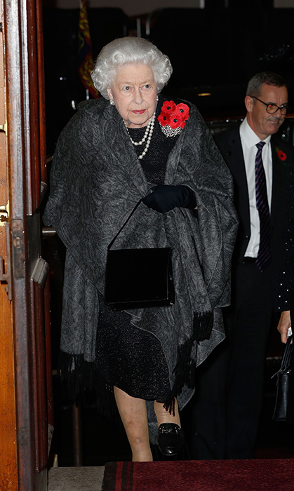 Her Majesty made a striking appearance at the Festival of Remembrance in a black textured dress with a pretty grey shawl draped over her shoulders and black heels. She donned two strands of pearls and carried her trusty black patent leather purse.