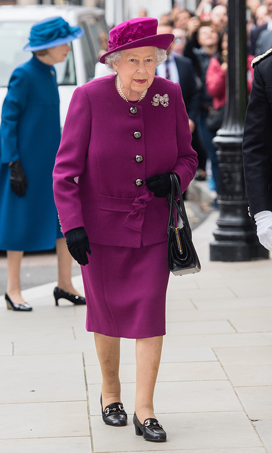The Queen looked fresh as a daisy at the Anglo-Norse Society Centenary Reception at the Naval and Military Club in London on Thursday (Nov. 15), the day after opening the doors of her palace to royalty from across Europe for her son Prince Charles' birthday party. Her Majesty wore a magenta suit with a bow belt paired with a matching hat and lip, along with black gloves and accessories, her three strands of pearls and a glittering bow brooch.
