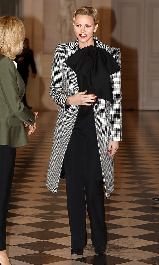 Princess Charlene did Parisian polish to perfection as she attended the Head of State's Partner Luncheon at the Chateau de Versailles on Nov. 11 alongside First Lady Brigitte Macron. The mother of two wore a Givenchy coat over an all-black ensemble featuring an oversized bow at the neck, adding a pop of colour courtesy of her red lip and nails. Tres chic!