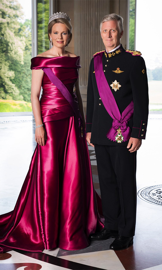 Hot on the heels of Prince Charles' birthday bash, Queen Mathilde of Belgium looked every inch the modern monarch in a new set of portraits released to mark Koningsdag, also known as the King's Feast, on Nov. 15. Standing beside her husband King Phillippe in his military uniform, the blonde beauty wore a custom off-shoulder Armani Prive taffeta gown in magenta with a dazzling tiara, diamond earrings and a matching bracelet.