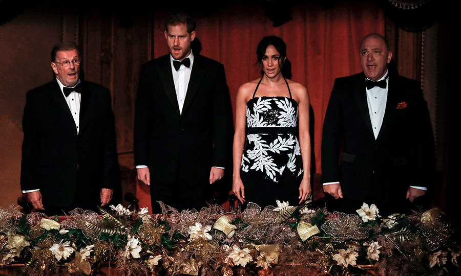 "Prince Harry and Meghan took their seats in the royal  box and sang along to ""God Save The Queen."" The evening's host, Greg Davies, had the couple in a fit of giggles when he joked about his grandmother wanting to marry Prince Harry before Meghan did.