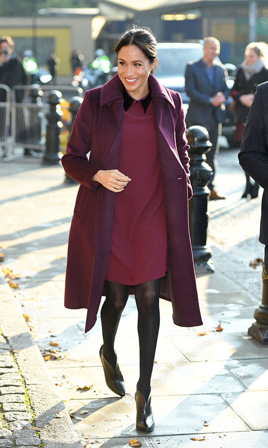 "Meghan looked radiant as she arrived at the kitchen clad in a burgundy ensemble by <a href=""/tags/0/club-monaco/"">Club Monaco</a>. She paired the brand's Sallyet dress, featuring a pretty velvet collar, with a coordinated wool coat, black tights and a chic pair of Givenchy boots. 