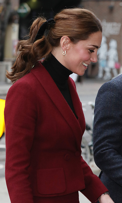 Mother-of-three Kate switched up her hairstyle from her classic bouncy waves, tying it back in a ponytail, kept high with a sweet velvet ribbon tied in a bow. She anchored the look with a pair of black block-heeled Tod's suede pumps and wore Asprey London's Oak Leaf earrings. The 36-year-old topped it all off with her usual pretty beauty look - taupe shadow and black lashes with rosy cheeks and a pink lip.