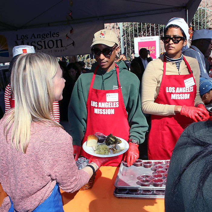 Pharrell Williams and his wife Helen Lasichanh put on their red aprons and helped hand out food at the Los Angeles Mission.