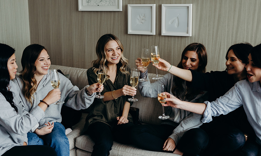 At the Four Seasons Hotel in Toronto, surrounded by her nearest and dearest friends since high school, Lauren raises a glass of champagne ahead of the wedding festivities.