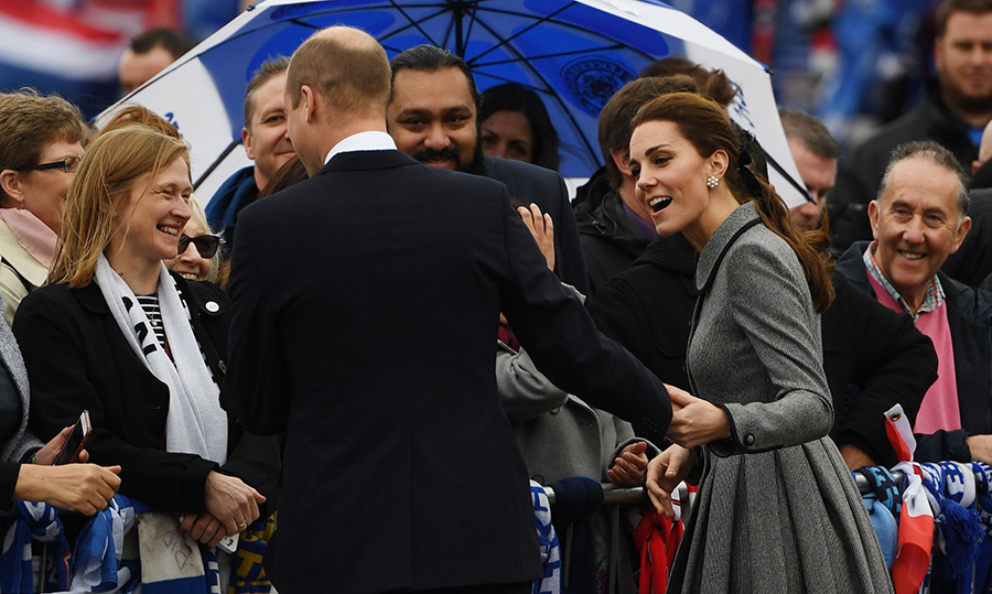 While greeting well-wishers who gathered at the stadium, Kate and William shared a playful moment, with the duchess grabbing her husband's hand. Something must've been funny!