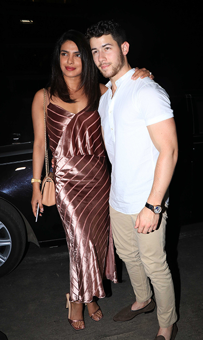 Priyanka stunned in a satin striped rose gold dress with matching metallic heels and a peach purse. Sided by her dapper husband, dressed simply in khakis and a white T-shirt, the two joined his brother Joe and his fiancee Sophie Turner for a night out.