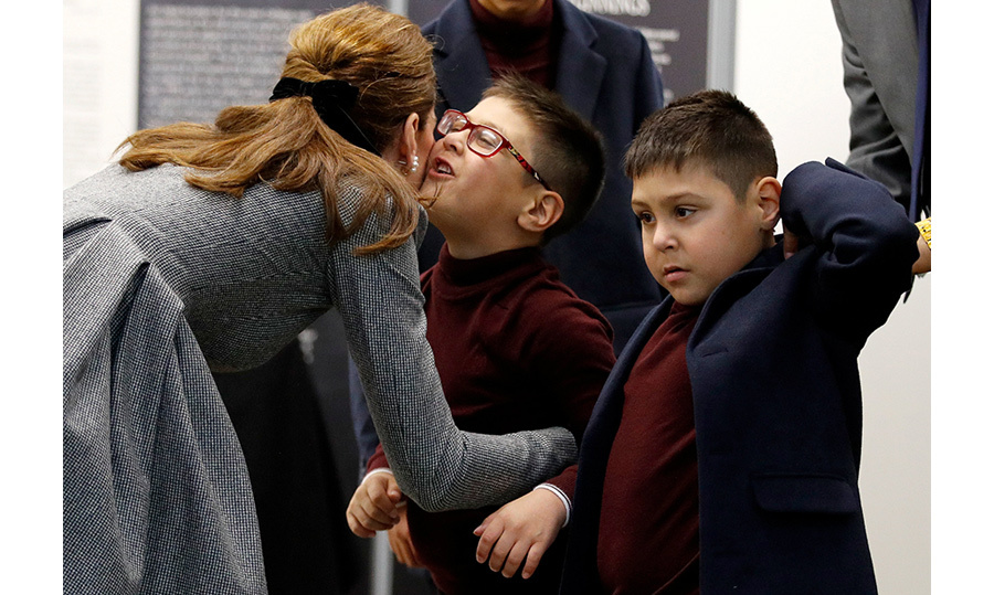 The Duchess of Cambridge greeted by Sai Gokani with a kiss on the cheek. The young boy has received help through a community project which received funding from Leicester City's owner, Vichai.