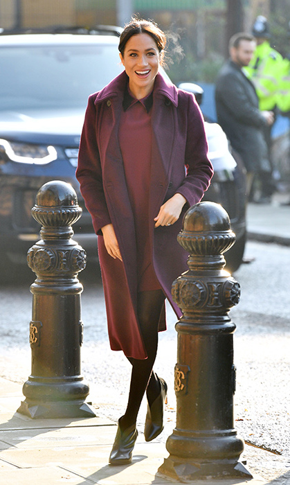 The Duchess of Sussex went with a burgundy shift dress by Club Monaco, paired with a matching coat by the label. She wore black tights and Givenchy boots for her visit to the Hubb Community Kitchen.