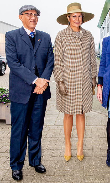 Máxima is the queen of accessorizing! She wore the chicest pair of metallic gold gloves and a matching hat to go along with her suede heels and amazing coat for a visit to a horticultural centre.
