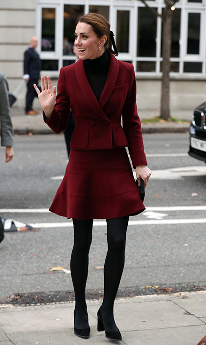 Duchess Kate looked chic as ever in an oxblood Paule Ka suit with a black turtleneck. She anchored the look with a pair of black suede Tod's pumps and wore her hair up in a ponytail secured by a ribbon – the perfect final touch to any holiday outfit this year!