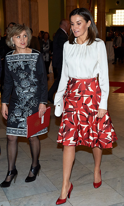 Queen Letizia turned to one of her favourite Carolina Herrera skirts for a hospital visit to Madrid, offering fans the perfect inspiration for holiday separates. She wore the knee-length floral number with a white blouse featuring a gathered neckline and red leather pumps.