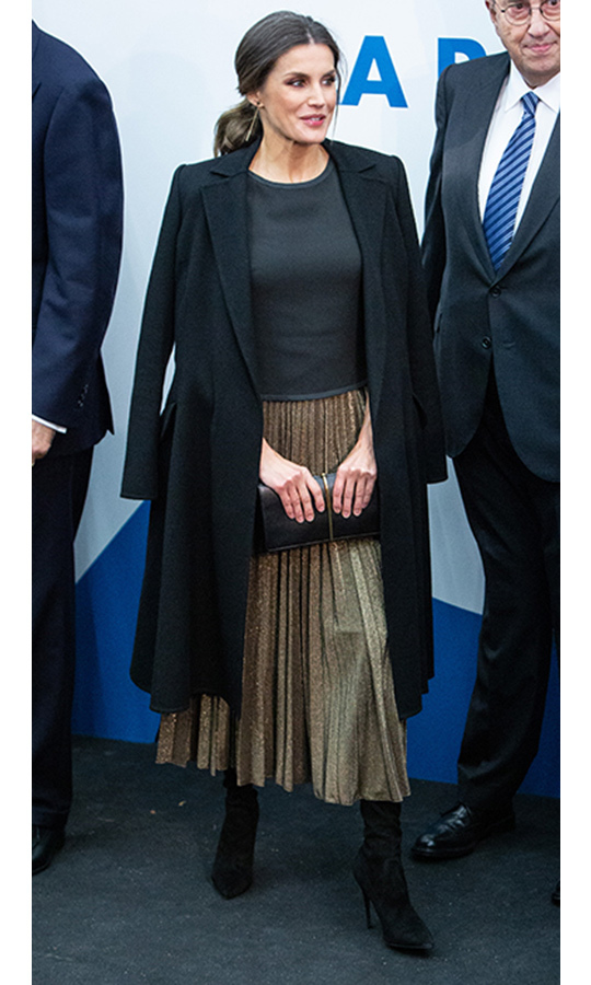 Queen Letizia was the ultimate golden girl in a pleated midi skirt by Zara, which she wore with black suede boots and a sleeveless black top. Toss a wool coat over your shoulders and your ready for any festive shindig!