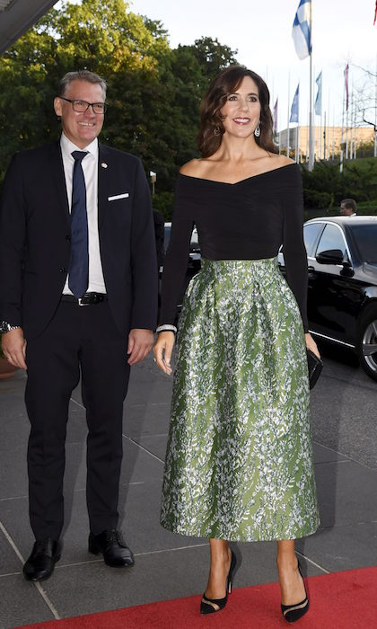 While visiting Helsinki, Crown Princess Mary wore a two-piece ensemble that is the stuff of holiday party dreams - an off-shoulder black top with a bell-shaped, metallic green ankle skirt and black pumps.