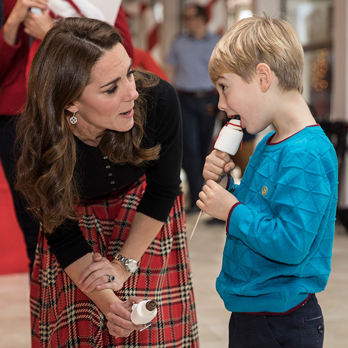 The duchess showed off her big heart while chatting with five-year-old Henry O'Grady, one of the children who's parent is serving overseas. The young boy happily munched on a candy snowman!