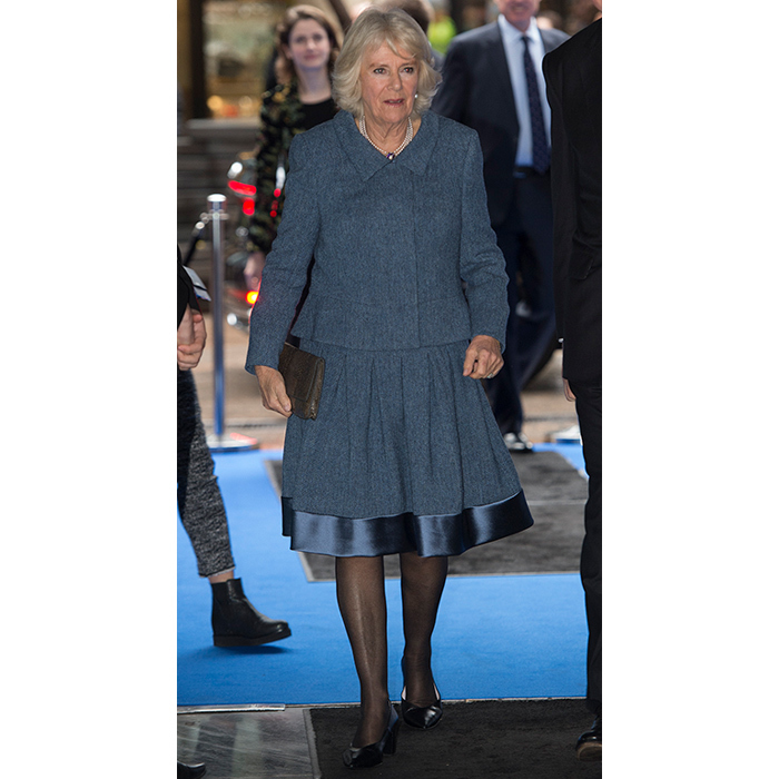 Camilla, Duchess of Cornwall, dazzled in a blue-grey skirt suit for a visit to the ICAP during the broker's 26th annual Charity Day on Dec. 5. Her ensemble featured a festive satin trim and she accessorized with a pair of black heels and a small clutch.