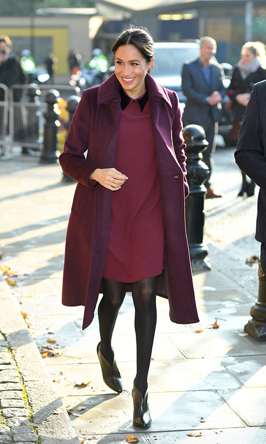 "Meghan dazzled in one of her favourite designers, the Canadian-founded <strong><a href=/tags/0/club-monaco>Club Monaco</a></strong>, for a surprise visit to the Hubb Kitchen in on Nov. 21, 2018. In a new colour and silhouette, the <i><a href=/tags/0/suits><strong>Suits</a></strong> alum chose the burgundy ""Sallyet"" dress, with its festive velvet collar, and the perfectly coordinated ""Daylina"" coat. 