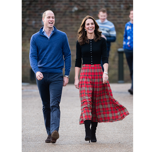 The Duke and Duchess of Cambridge were in high spirits on Tuesday (Dec. 4) as they opened up the Orangery at Kensington Palace for a Christmas party with the families of military personnel stationed in Cyprus. The parents of three were keen to honour the work of servicemen and women who are away from their families over the festive season - and have some fun with their partners and children, from a photo booth that sent snaps directly to Cyprus to Christmas crafts like decorating snow globes and making crackers. Prince William and Kate looked wonderful for the occasion, he in a blue sweater and slacks and she in a plaid skirt by one of her go-to designers, Emilia Wickstead, with black accessories.
