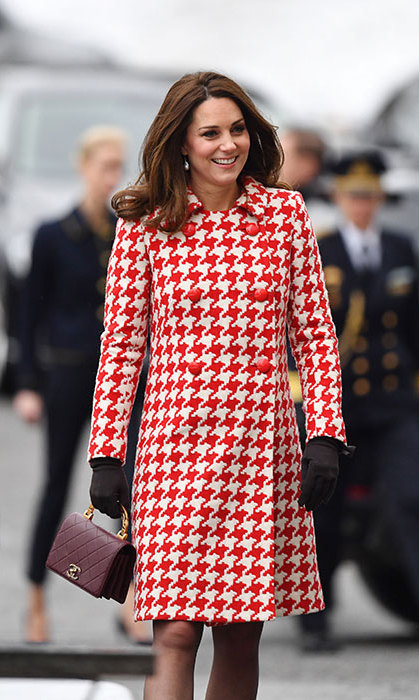 While visiting the Karolinska Institute in Sweden with Crown Princess Victoria and Prince Daniel, Kate wore a stylish red and white coat by Catherine Walker, which not only looked warm and comfortable in the cold climate, but made a bold style statement. She wore a dress by Alexander McQueen and earrings by Swedish designer In2Design and toted a Chanel bag.