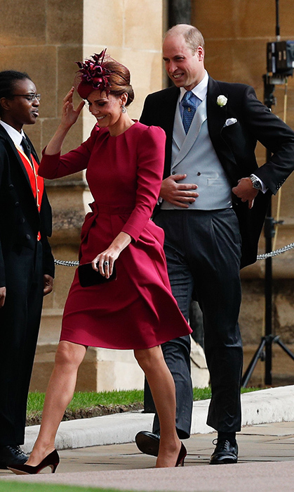 Duchess Kate brought some colour to Princess Eugenie's wedding on Oct. 12 in a fuchsia dress by Alexander McQueen, which resembled the look she wore in cream to Prince Louis' christening. Kate paired her dress with a matching fascinator featuring a small floral arrangement on one side, with netting on the other. She went with one of her classic styles of pump in a deep wine hue, finishing the look with a black clutch.