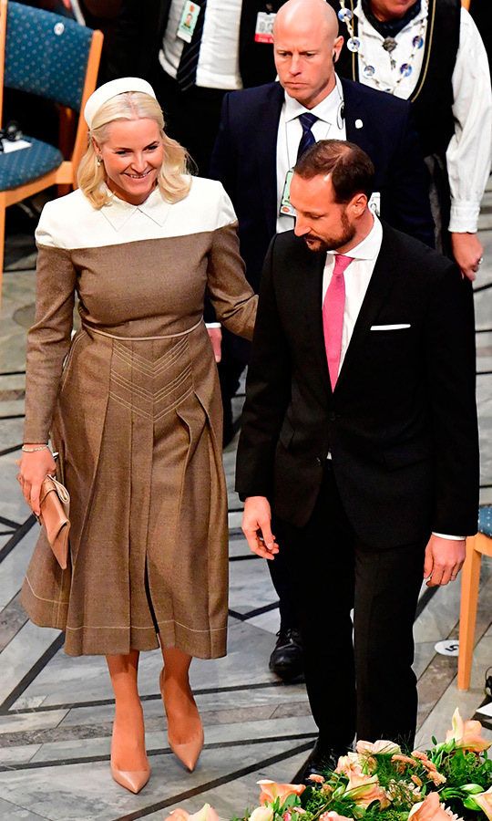 Princess Mette-Marit attended the Nobel Peace Prize ceremony in Oslo on Dec. 10 looking the picture of elegance. The mother of three wore a brown long-sleeved dress with white shoulders and collar and a pleated skirt, which she paired with a white pillbox hat, nude pumps and a sleek clutch. 