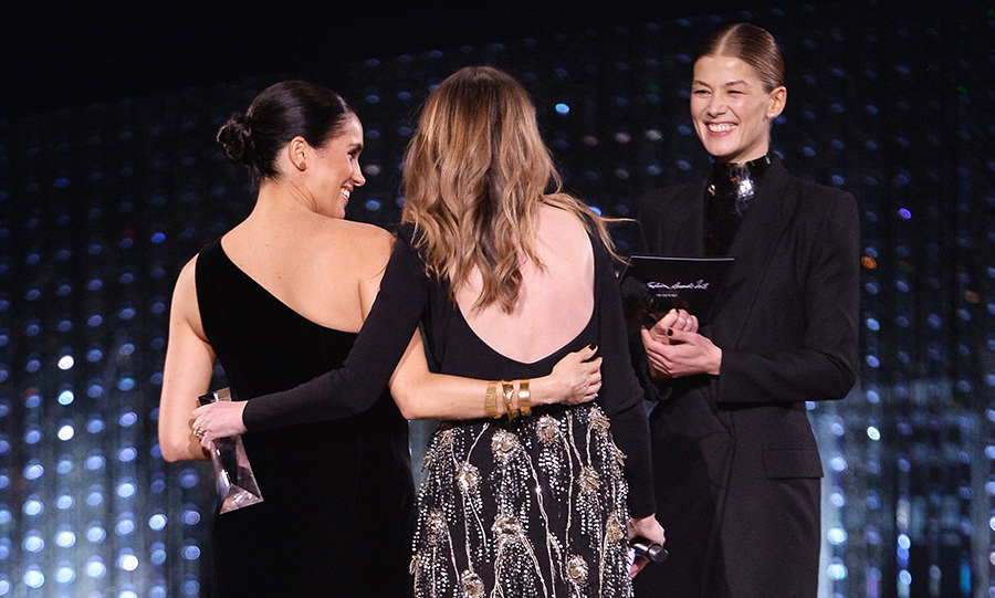 After she accepted her award, Meghan gave the British designer a tight squeeze as the <em>Gone Girl</em> actress looked on. Clare wore a stunning black backless long-sleeve top with a glitzy bejewelled skirt.