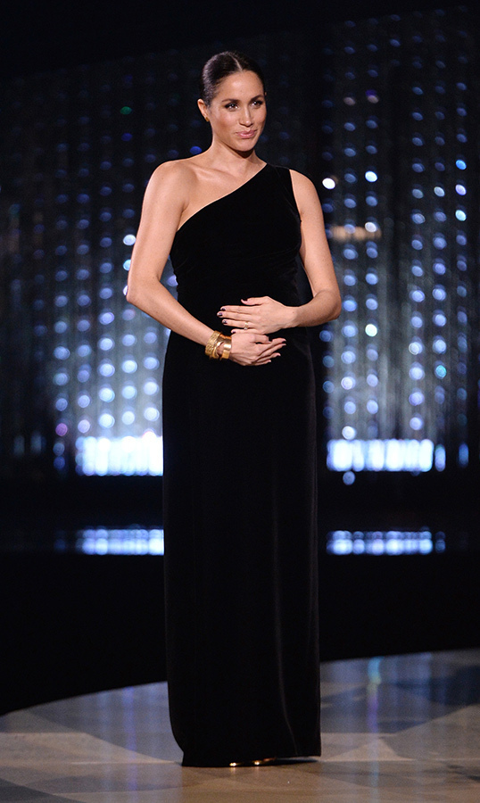 The Fashion Awards in London enjoyed a surprise visit from Duchess Meghan and a growing Baby Sussex! The mom-to-be was on hand to award Clare Waight Keller, the designer of her wedding gown, the designer of the year prize. Meghan dazzled in a one-shoulder black velvet gown crafted by Clare, stacked gold bracelets by Pippa Small and metallic sandals by Tamara Mellon. She slicked her brunette hair back in a low bun.