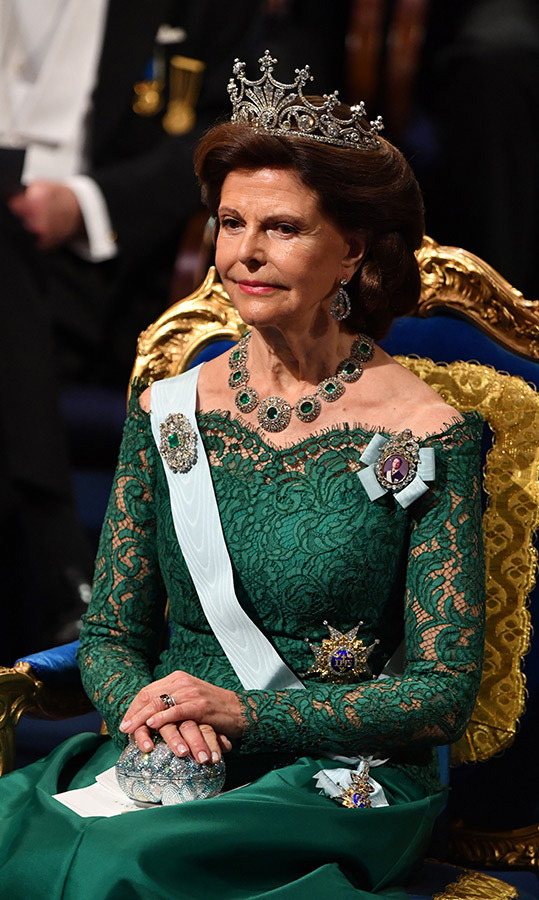 Queen Silvia wore a gorgeous green gown with a lacy, off-shoulder bodice and satin skirt. The design was perfectly paired with her diamond and emerald necklace, but the piece de resistance was definitely the sparkling tiara perched on her brown locks. The mother of three carried a shimmering egg-shaped clutch bag and wore a swipe of pink lipstick.