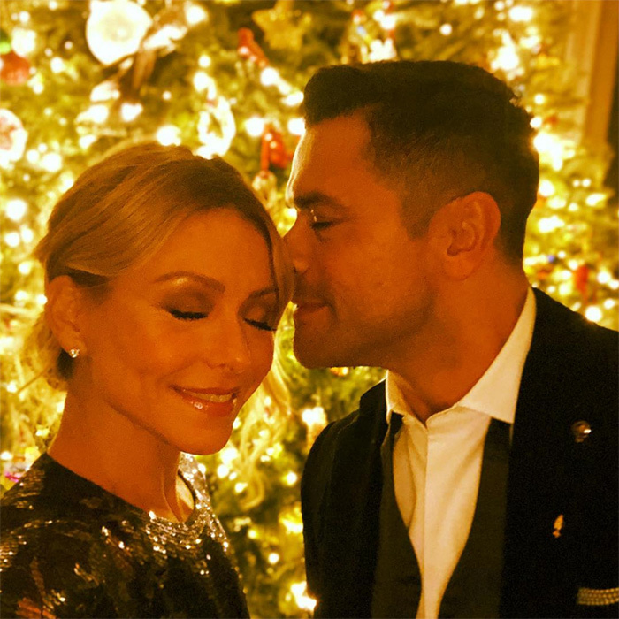 We love these tender holiday moments, especially when they're between enduring Hollywood couple Kelly Ripa and Mark Consuelos! Merry kiss-mas!
