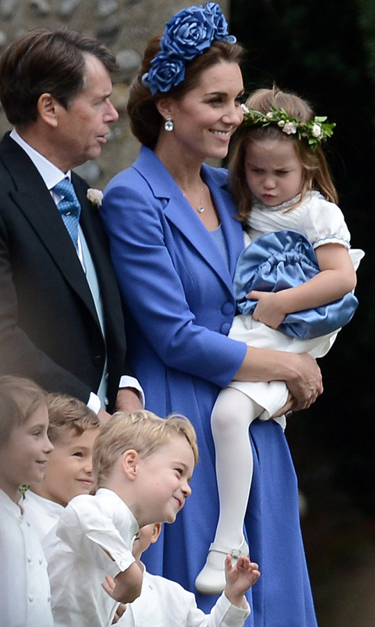 Princess Charlotte, in her white bridesmaid ensemble and floral garland, was not impressed with Prince George as he goofed around for the camera at Sophie Carter's wedding, to the delight of his fellow pageboys. The three-year-old scowled at her big brother. 