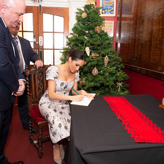 Prince Harry's wife signed the home's guestbook in her gorgeous script.