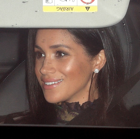 A closer view of Duchess Meghan showed off her stunning beauty look, topped off with a swipe of pale pink lipstick and a subtle brow. She appears to be wearing a black ruffled high-neck top, along with her dark hair in a sleek, straight style.