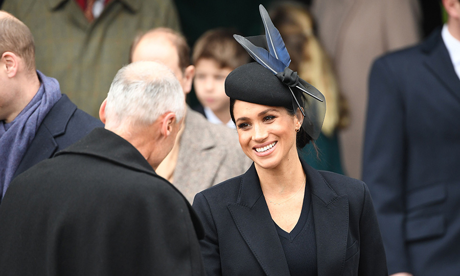 Meghan was definitely sporting her pregnancy glow! The mom-to-be wore dark liner and mascara on her eyes and a pretty pink lip and swept her hair up into a side bun under her pretty feathered hat.
